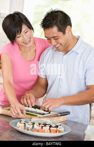 Couple Preparing Sushi Together - Stock Photo