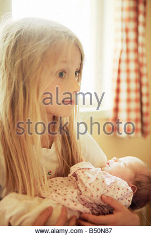Close up of a girl carrying her sister - Stock Photo
