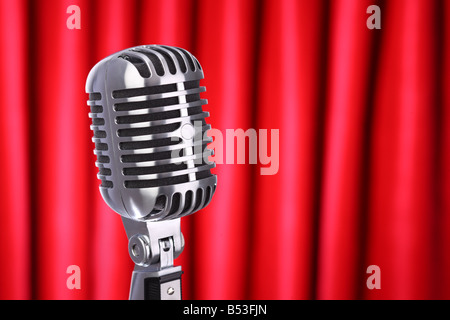 Close up of classic retro microphone with red curtain background - Stock Photo