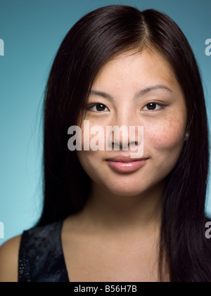Close-up portrait of young and confident Chinese woman in a studio setting - Stock Photo