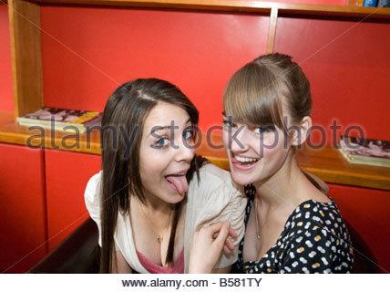 Teenage girls making faces in cafe - Stockfoto
