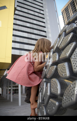 Young girl child climbing on sculpture outside Brisbane Square new modern City Council building in Brisbane Queensland - Stock Photo