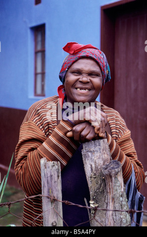 Mature woman smiling Missing top teeth Blue house wall WOMAN SWAZILAND - Stock Photo