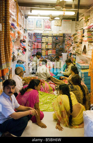 Women shopping and buying saris in a sari shop in the Kinari market, Old Delhi India - Stock Photo