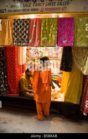 A Woman buying saris in a shop in the Kinari market, 'Old Delhi' India - Stock Photo