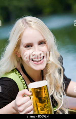 Germany, Bavaria, Munich, English Garden, Young woman holding beer stein, portrait, close-up - Stock Photo