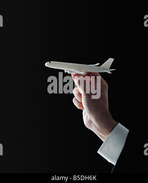 Model Aeroplane in the Hand of a Businessman Against Black Background - Stock Photo