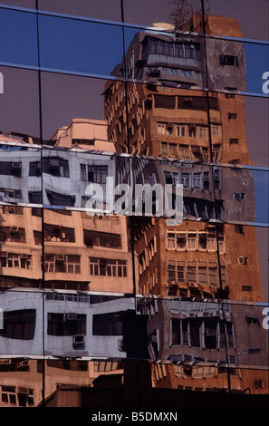 Old buildings reflected in glass facade of new building hong kong sar chin fareast asia - Stock Photo