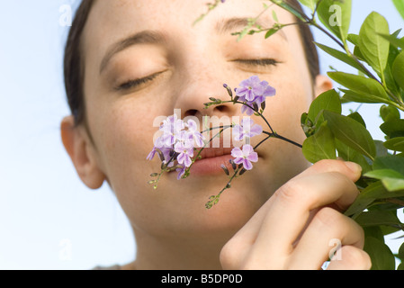 Young woman smelling small purple blossoms on flowering tree - Stock Photo