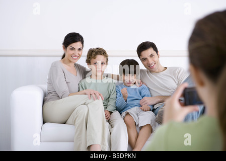 Family sitting on sofa, posing for photo being taken by daughter - Stock Photo