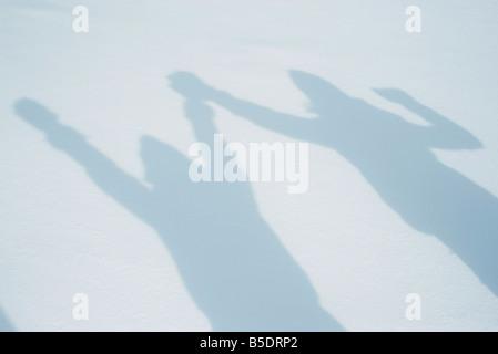 Schatten von Menschen, die Arme auf Schnee - Stockfoto