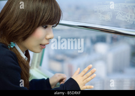 Young woman on Ferris wheel, looking out window - Stockfoto