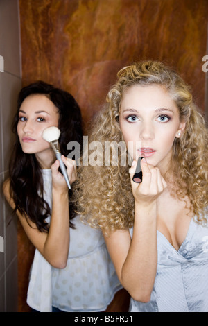 girls doing make-up in bathroom - Stock Photo
