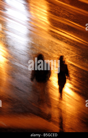 two people walking in heavy rain at night in town - Stock Photo