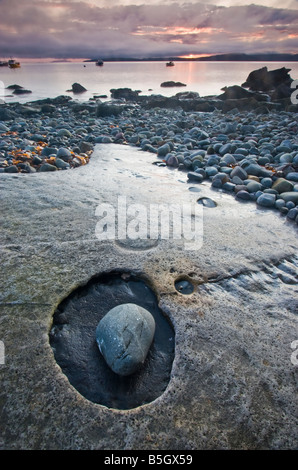 Incredible eroded limestone sheets and pebbles on Elgol beach, with the harbour in the background. - Stock Photo
