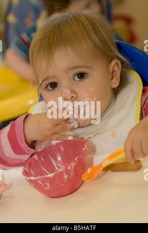 young baby toddler child in nursery day care centre toddler eating yoghurt messily wearing bib, messy face, UK - Stock Photo