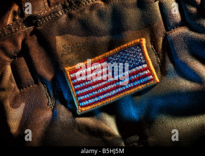 Detachable US flag patch on military camouflage fabric. Mirrored flag is for right shoulder. - Stock Photo