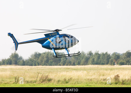 Hughes 369D 500 G-ERIS helicopter landing at Sandtoft Airfield - Stock Photo