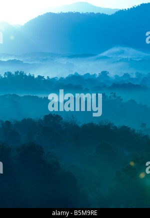 Misty morning of hilly area with ray of light. - Stock Photo