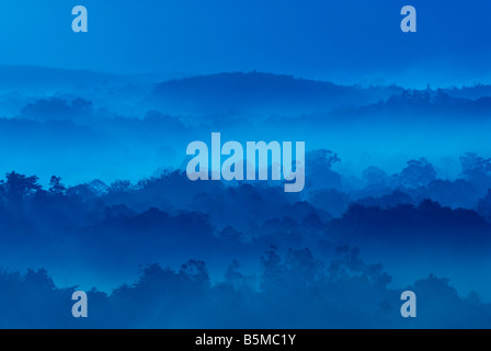 Misty morning of hilly area with ray of light - Stock Photo