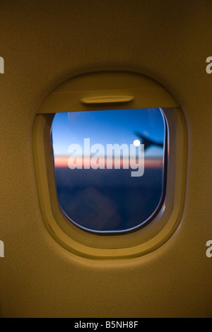 TWILIGHT VIEW THROUGH COMMERCIAL AIRLINER PASSENGER CABIN WINDOW FRAME - Stock Photo