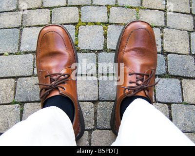 A man's feet in brown shoes - Stock Photo