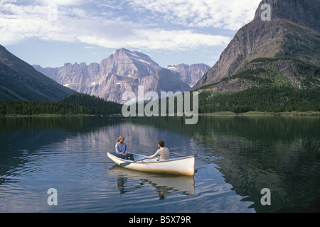 Two young people take a ride in a rowing dory on Swiftcurrent Lake near Many Glacier Hotel, Glacier National Park - Stock Photo