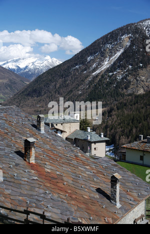 Stone tiled roofs of italian village against alpine mountains snow peak with clouds in the background - Stock Photo