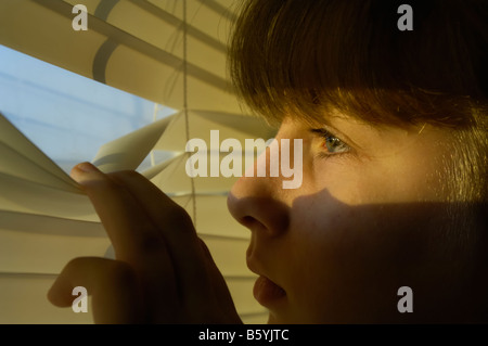 Sad and depressed teen girl looks outside her window, into the sunshine, from the darkness of her room.  Photo by - Stockfoto