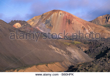 Colourful mountain landscape looking over the lava field of Laugar, Laugarhaun, towards a mountain of Rhyolite, - Stock Photo