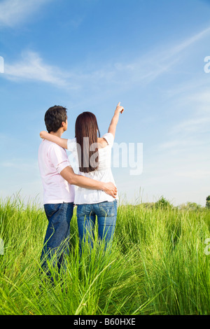 young couple in meadow with hand in air - Stock Photo