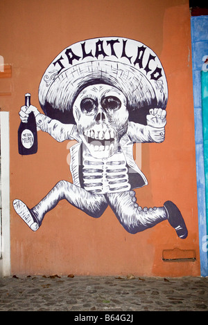 Oaxaca, Mexico. Day of the Dead.  Wall Mural of Running Skeleton Holding a Bottle of Mezcal, a Local Alcoholic Liquor. - Stock Photo