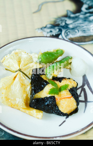 Japanese cuisine, yuba (bean curd skin), tofu wrapped in nori and hot pepper tempura on plate - Stock Photo