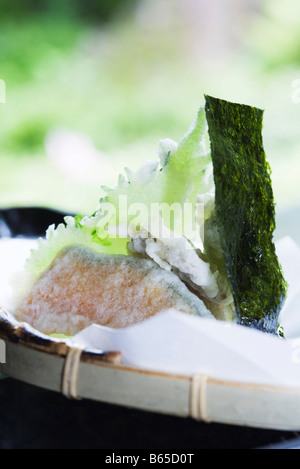 Winter squash and shiso tempura with piece of nori, close-up - Stock Photo