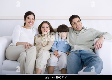 Family sitting together on sofa, looking away - Stock Photo