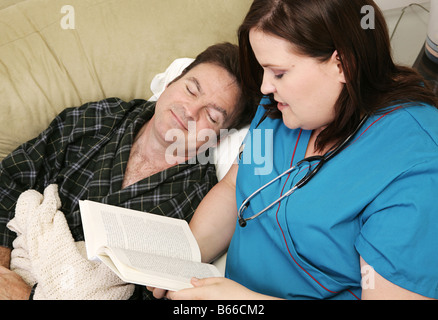 Home health nurse reading to her patient as he falls asleep Focus on nurse - Stockfoto
