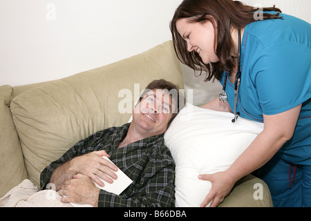 A home health nurse fluffing the pillow of a sick man Focus on man s grateful face - Stockfoto