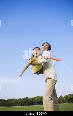 Young father holding daughter up in the mid air - Stockfoto