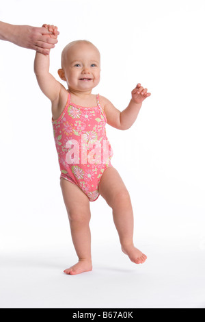 Baby girl setting first steps - Stock Photo
