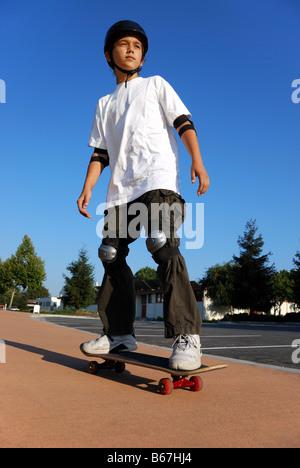 Boy on a Skateboard Against Blue Sky Looking in the Sun - Stock Photo