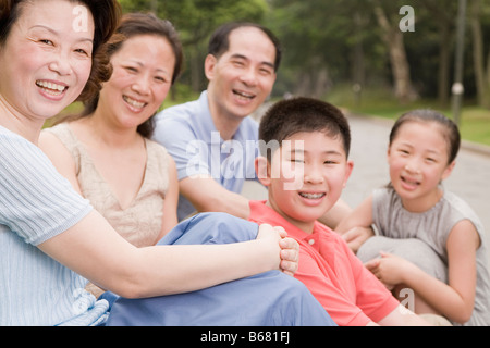 Portrait of a three generation family sitting together in a garden - Stock Photo
