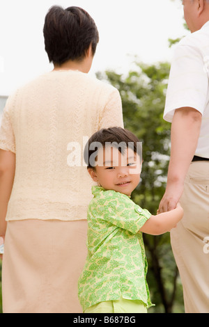 Portrait of a boy walking with his grandparents - Stock Photo