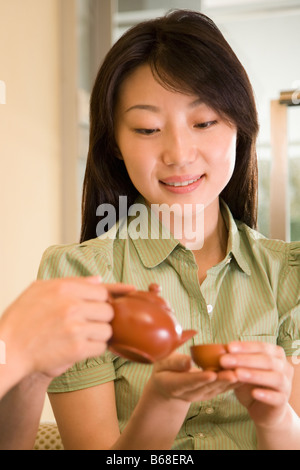 Close-up of a person's hands pouring tea into a cup held by a young woman - Stock Photo