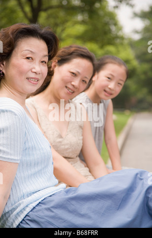 Portrait of a three generation family sitting and smiling in a garden - Stock Photo