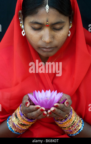 Indian woman offering a Nymphaea Tropical waterlily flower in a red sari - Stock Photo