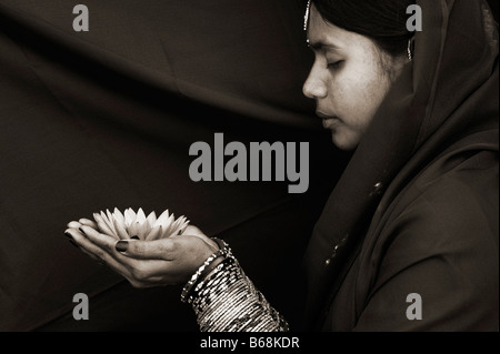 Indian woman offering a Nymphaea Tropical waterlily flower. Sepia Tone - Stock Photo