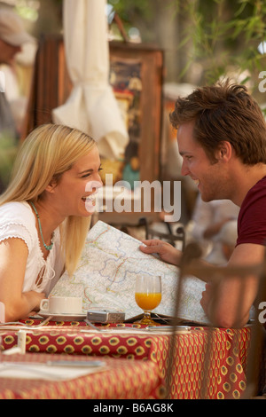 Couple laughing in french market cafe - Stock Photo