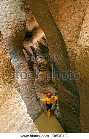 Climber explores the Key Hole slot canyon Zion National Park near Springdale Utah. - Stock Photo