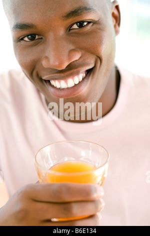 Man drinking orange juice. - Stock Photo