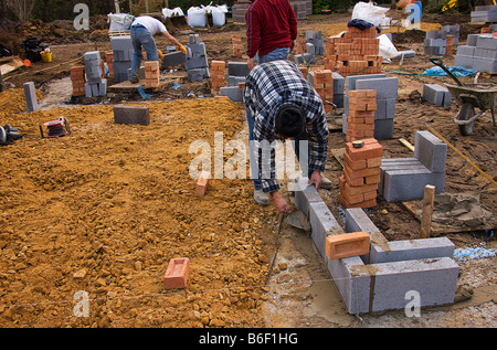 Laying the first row of concrete blocks starting at one of the corners. - Stock Photo